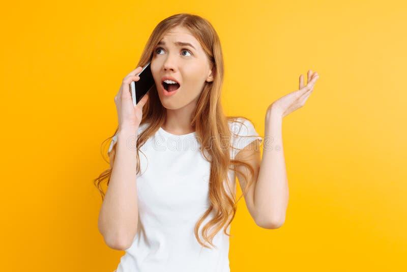 Ragazza irritata ed incerta che parla sul telefono, su un fondo giallo fotografia stock libera da diritti