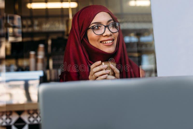 Ragazza islamica graziosa nel hijab alla caffetteria immagine stock libera da diritti