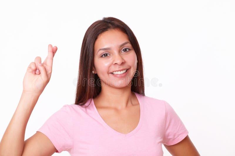 Ragazza ispanica amichevole che attraversa le sue dita fotografia stock libera da diritti