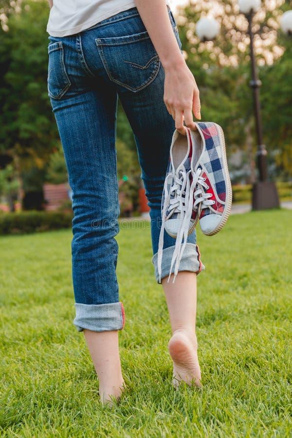 Ragazza in jeans che tengono le scarpe da tennis in sua mano fotografia stock
