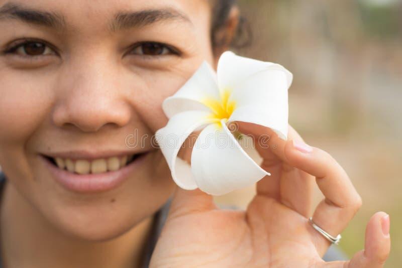 Ragazza khmer cambogiana asiatica sveglia dolce sorridente felice che tiene il fiore bianco e giallo di plumeria di Champey fotografia stock libera da diritti