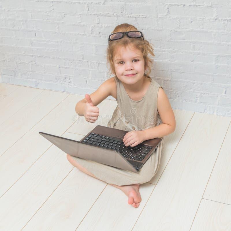 Ragazza, la donna di affari del bambino che lavora ad un computer portatile, contro un muro di mattoni bianco fotografia stock libera da diritti