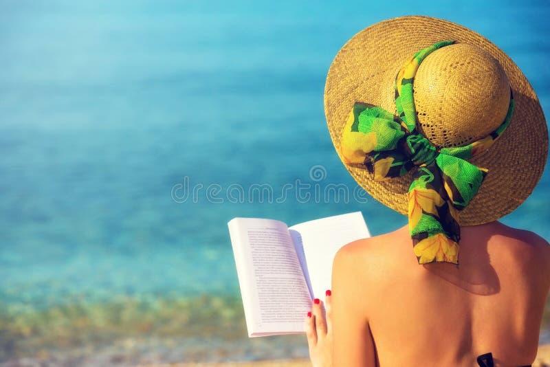 Ragazza, leggente un libro alla spiaggia fotografie stock