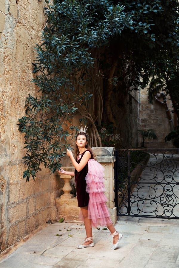 Ragazza leggiadramente di principessa nella libbra e corona che camminano attraverso il giardino del castello antico della città immagine stock libera da diritti
