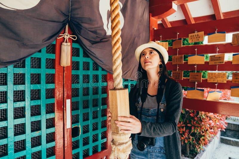 Ragazza locale che tira il tempio della corda in rosso immagine stock libera da diritti