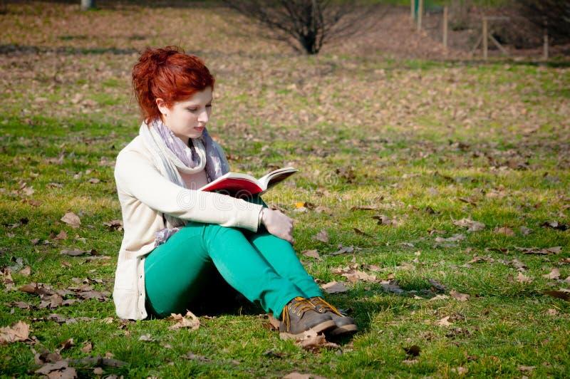 Ragazza lunga rossa dei capelli alla lettura del parco immagini stock libere da diritti