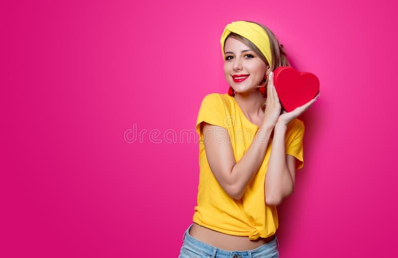 Ragazza in maglietta gialla con la scatola di forma del cuore immagine stock