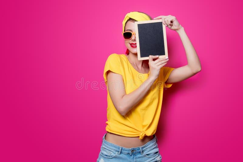 Ragazza in maglietta gialla con poca lavagna immagini stock