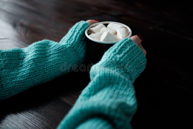 Ragazza in maglione blu che tiene tazza di caffè con le caramelle gommosa e molle Han immagini stock