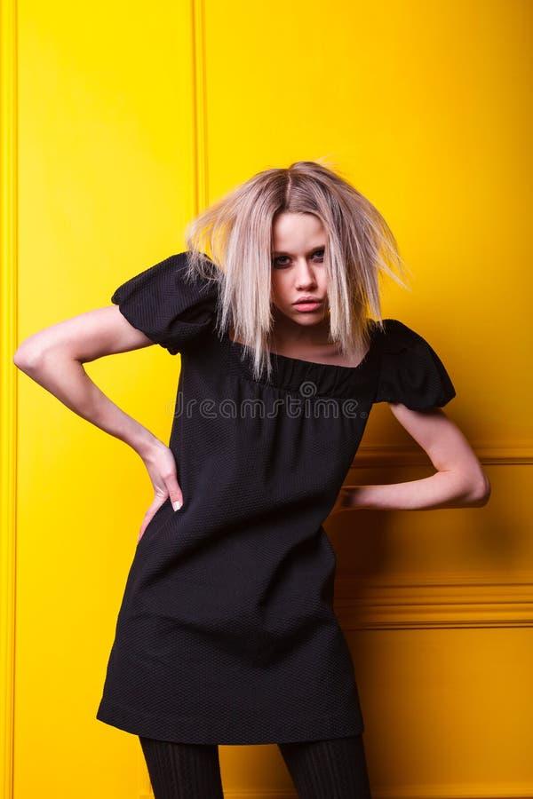 Ragazza magra che posa sul fondo giallo fotografia stock libera da diritti