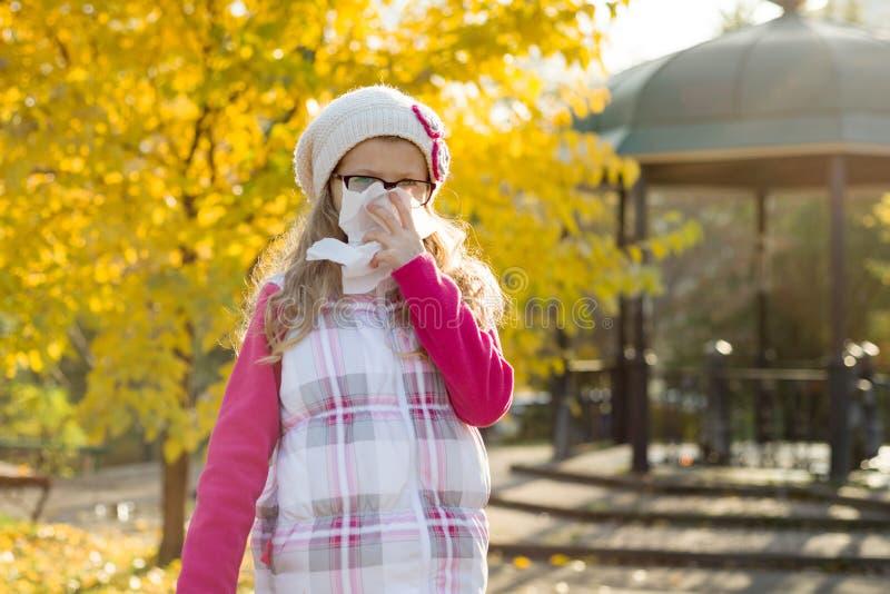 Ragazza malata congelata con un fazzoletto, alberi gialli di autunno del fondo fotografia stock
