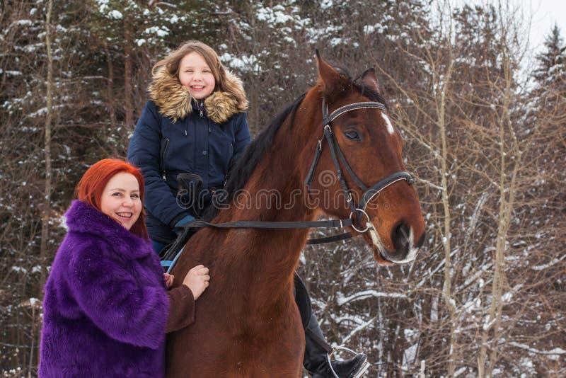 Ragazza, mamma e cavallo dell'adolescente in un inverno fotografia stock libera da diritti