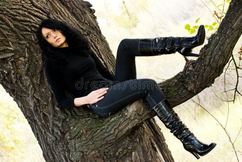 Ragazza Melancholic che si siede sull'albero immagine stock libera da diritti