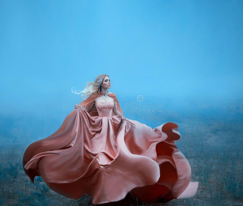 Ragazza meravigliosa con capelli bianchi biondi biondi e le caratteristiche molli di stupore mentre correndo, vestita in una pesc fotografie stock