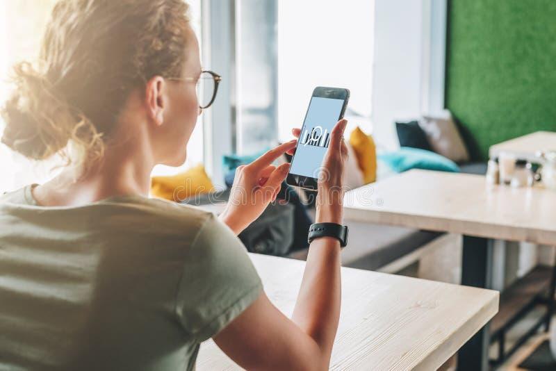 Ragazza millenaria che per mezzo dello smartphone e considerando il suo schermo con analisi statistica dell'iscrizione sullo sche immagini stock