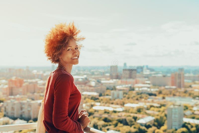 Ragazza mista riccia sul balcone con paesaggio urbano dietro immagine stock