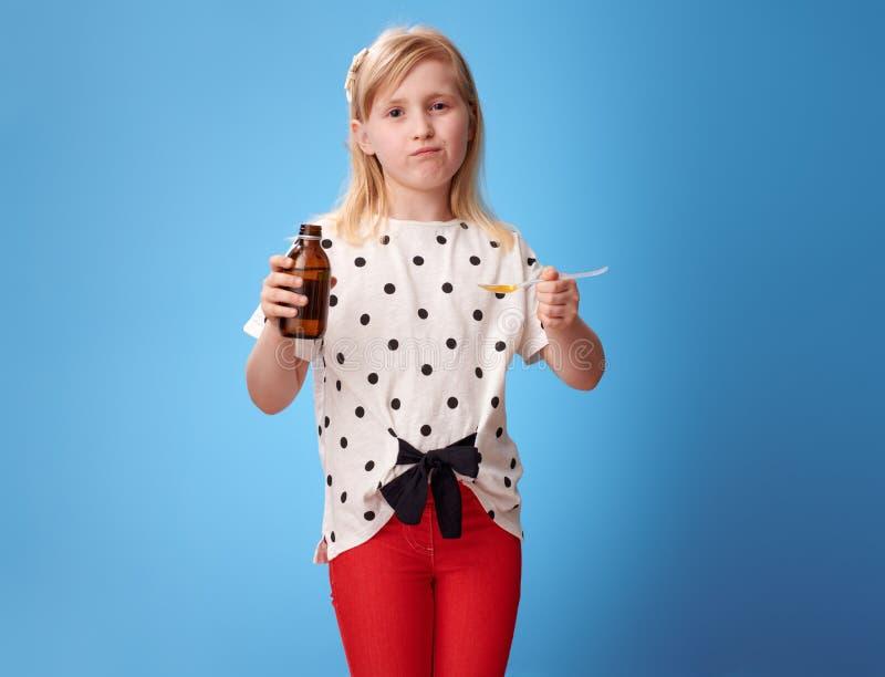 Ragazza moderna triste che prende cucchiaio della sospensione dei bambini sul blu fotografie stock libere da diritti