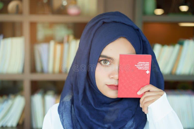 Ragazza musulmana che mostra un passaporto svizzero fotografie stock