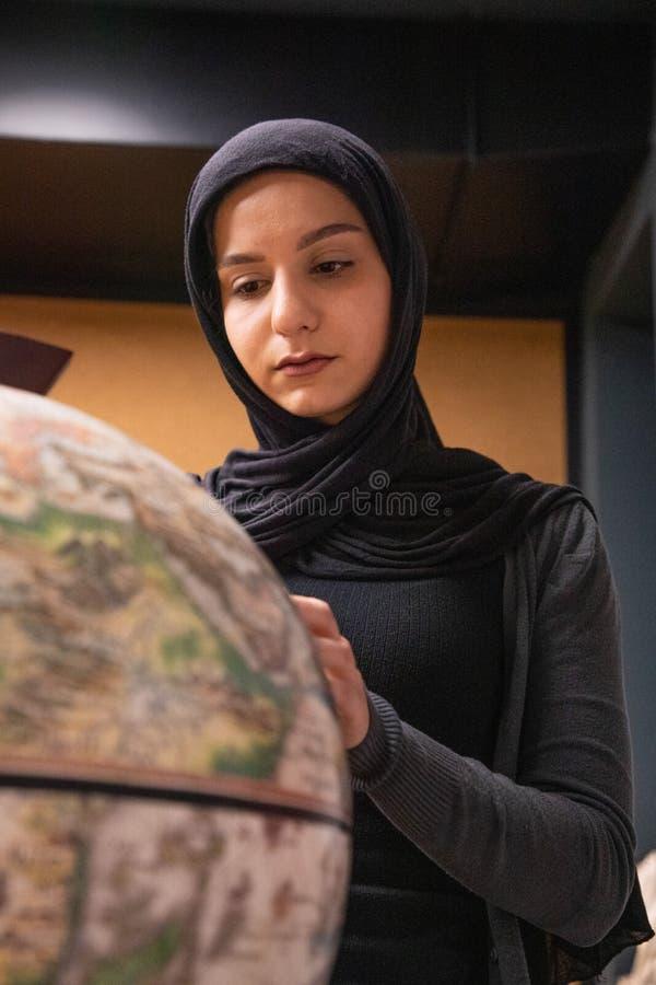 Ragazza musulmana che studia nella biblioteca fotografia stock libera da diritti