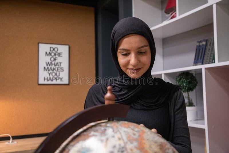 Ragazza musulmana che studia nella biblioteca fotografie stock libere da diritti