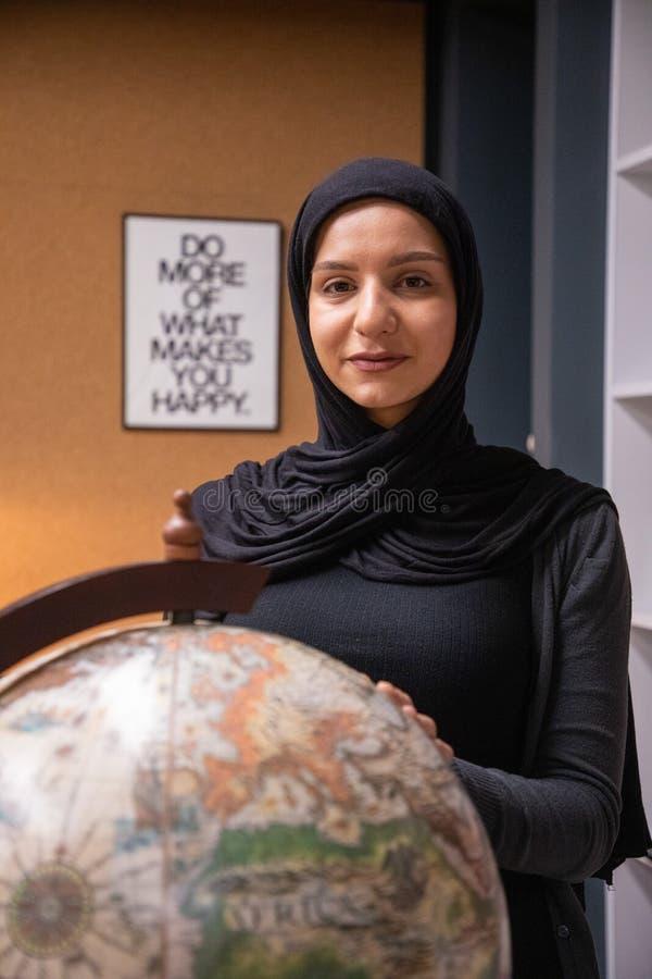 Ragazza musulmana che studia nella biblioteca immagini stock libere da diritti