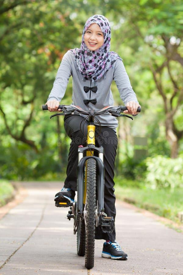 Ragazza musulmana sulla bicicletta fotografia stock