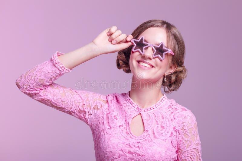 Ragazza negli smorfie di amore e posa divertente su un fondo rosa con le stelle di vetro rosa immagini stock