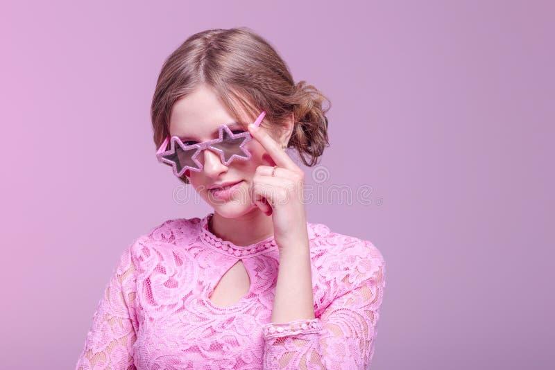 Ragazza negli smorfie di amore e posa divertente su un fondo rosa con le stelle di vetro rosa immagini stock libere da diritti