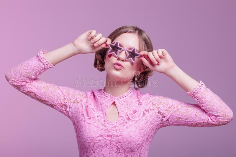 Ragazza negli smorfie di amore e posa divertente su un fondo rosa con le stelle di vetro rosa fotografia stock