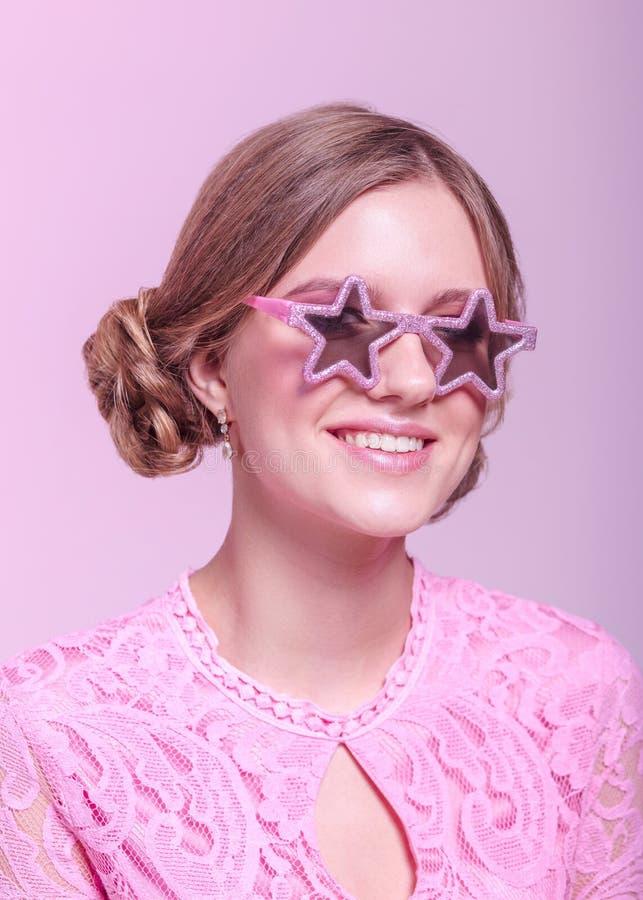 Ragazza negli smorfie di amore e posa divertente su un fondo rosa con le stelle di vetro rosa immagine stock