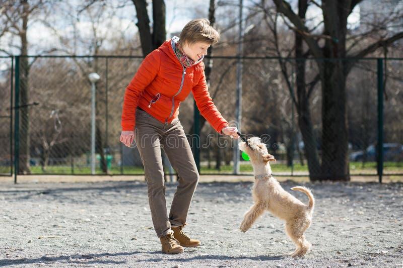 Ragazza nei giochi arancio del rivestimento con il cucciolo fotografie stock libere da diritti