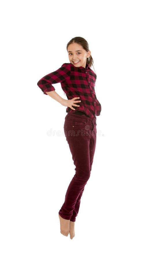 Ragazza nei salti dei pantaloni e della camicia fotografia stock