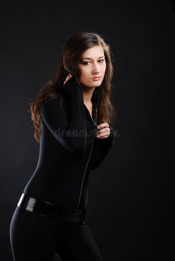 Ragazza nel catsuit nero contro i precedenti scuri. fotografia stock