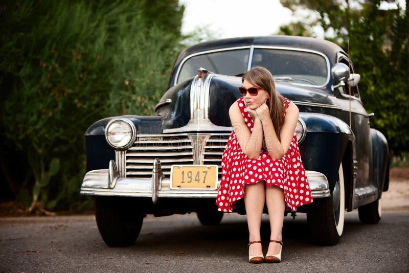 Ragazza nel colore rosso con l'automobile dell'annata immagine stock libera da diritti