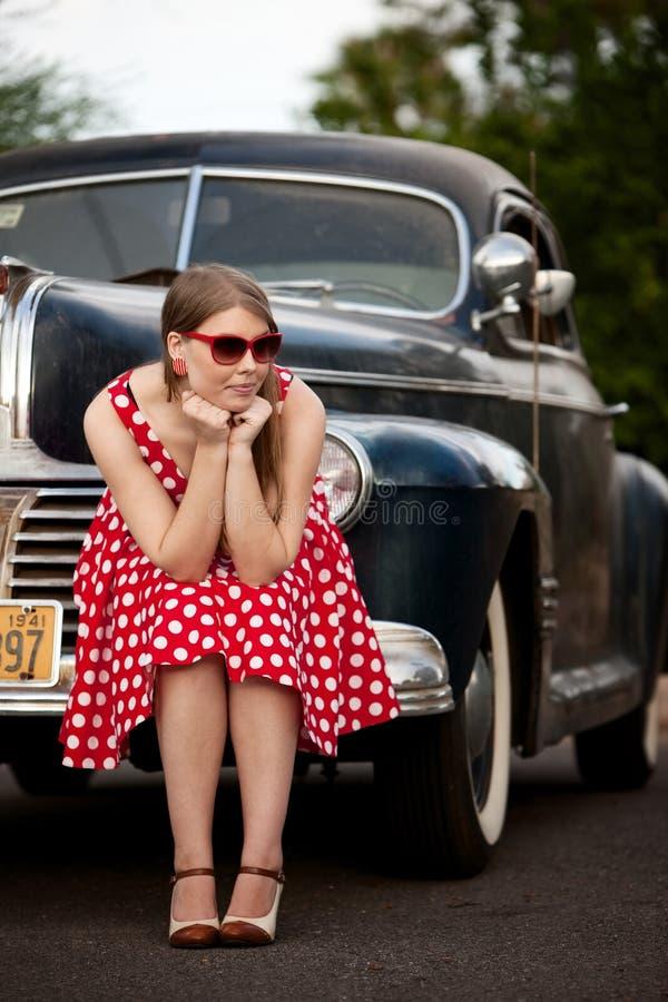 Ragazza nel colore rosso con l'automobile dell'annata fotografie stock