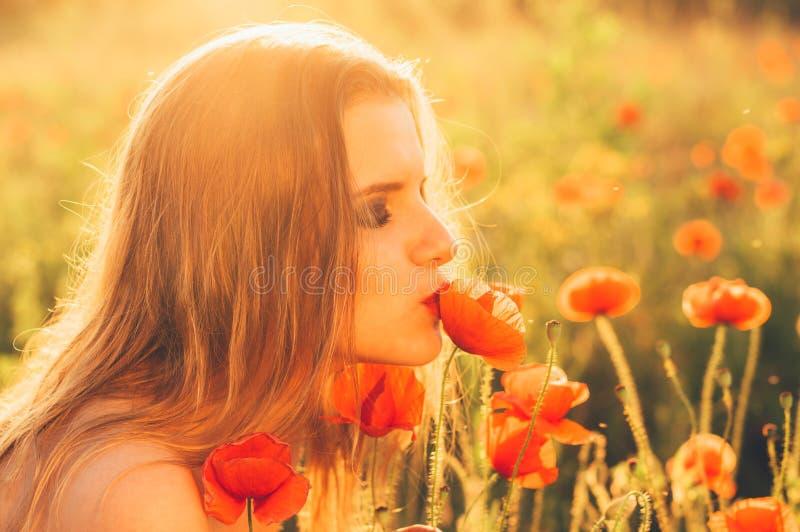 Ragazza nel fiore baciante del papavero del campo immagine stock