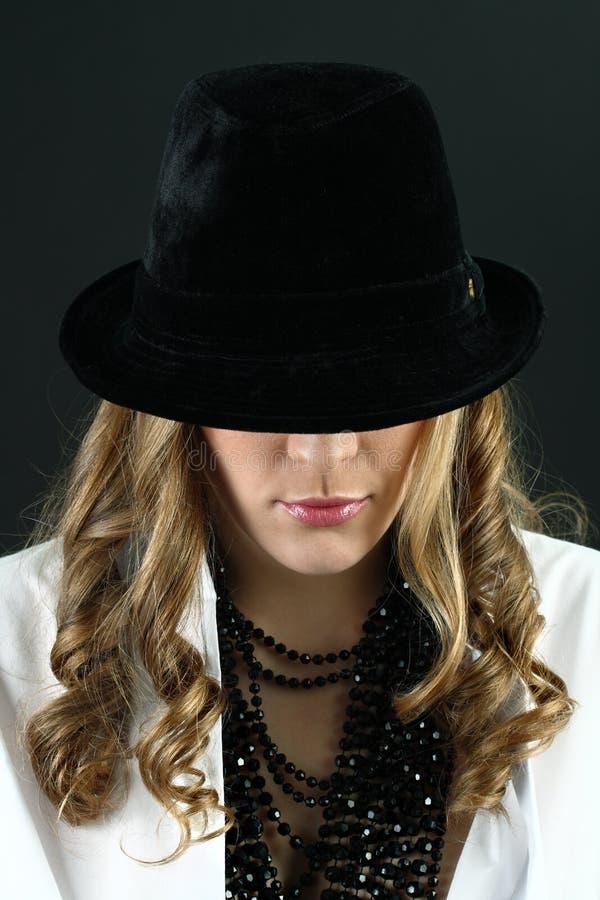 Ragazza nel fronte nascondentesi della camicia bianca sotto il cappello nero fotografie stock libere da diritti