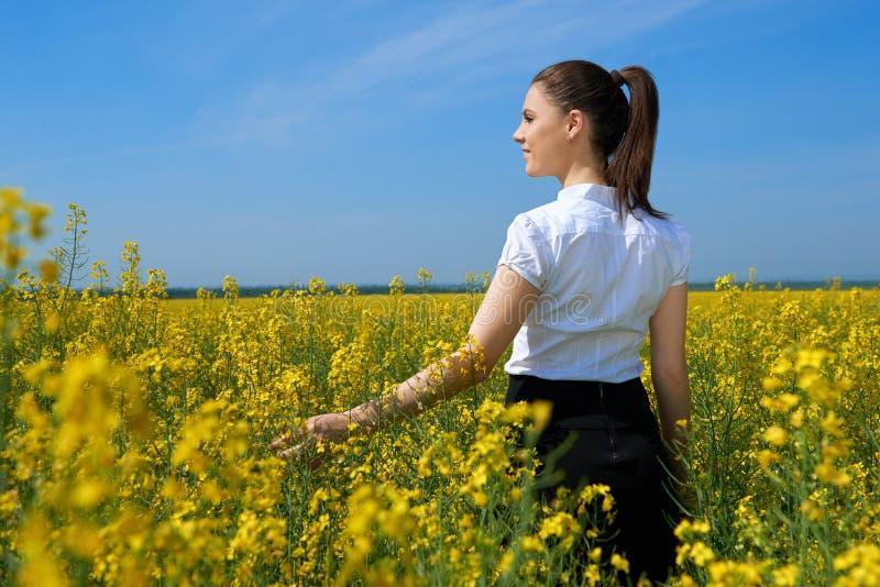 Ragazza nel giacimento di fiore giallo, bello paesaggio della molla, giorno soleggiato luminoso, seme di ravizzone fotografia stock
