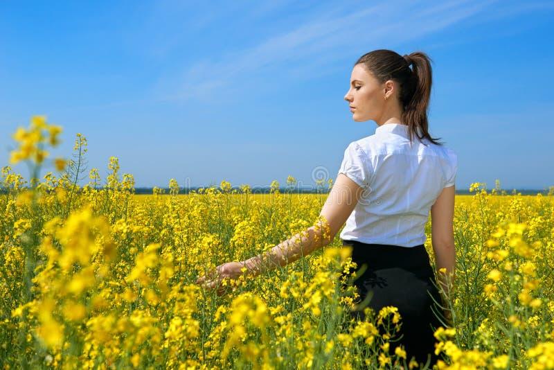 Ragazza nel giacimento di fiore giallo, bello paesaggio della molla, giorno soleggiato luminoso, seme di ravizzone immagini stock libere da diritti