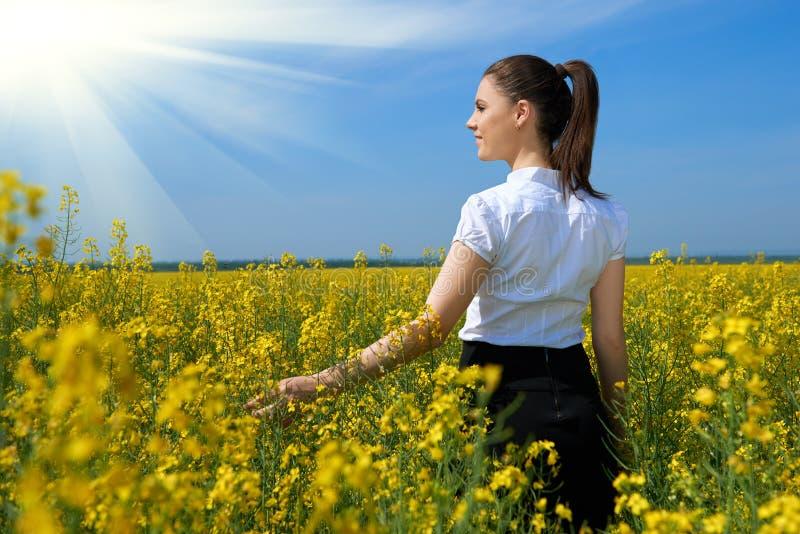 Ragazza nel giacimento di fiore giallo con il sole, bello paesaggio della molla, giorno soleggiato luminoso, seme di ravizzone fotografie stock libere da diritti