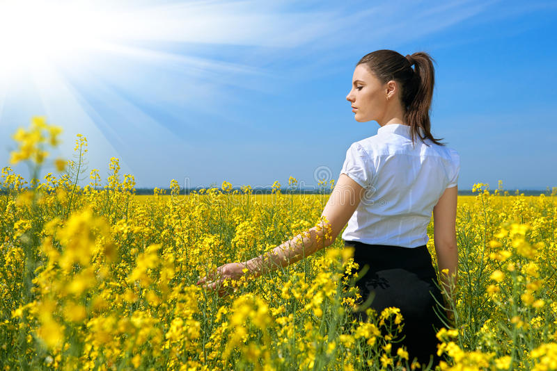 Ragazza nel giacimento di fiore giallo con il sole, bello paesaggio della molla, giorno soleggiato luminoso, seme di ravizzone immagini stock