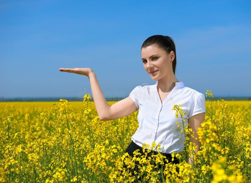 Ragazza nel giacimento di fiore giallo Mostri la palma Tenga in palma di qualcosa e sorrida Bello paesaggio della molla, giorno s immagine stock libera da diritti
