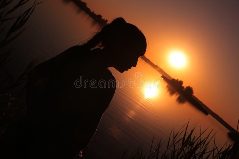 Ragazza nel lago al tramonto fotografia stock
