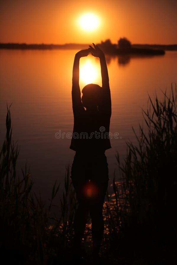 Ragazza nel lago al tramonto fotografie stock