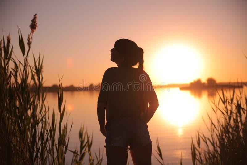 Ragazza nel lago al tramonto immagine stock libera da diritti