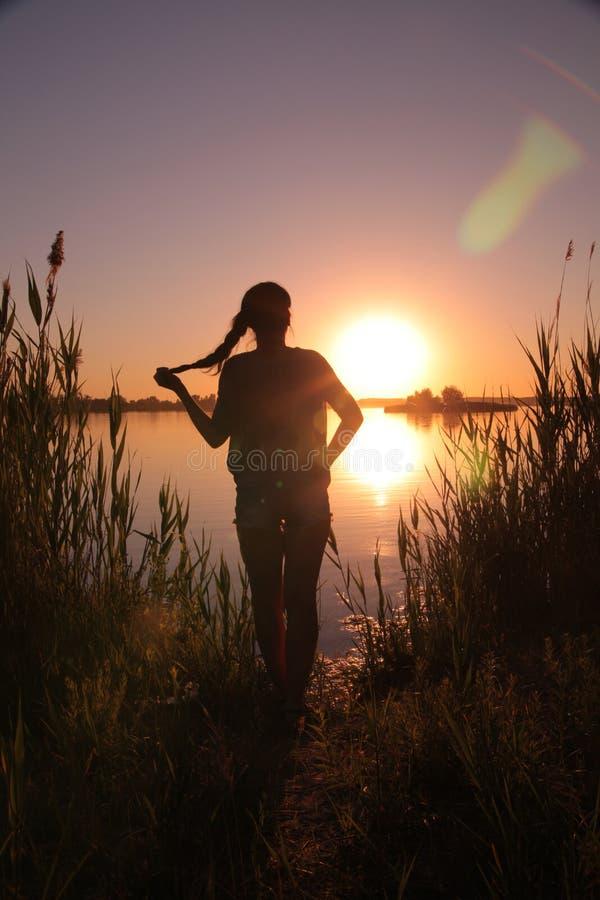 Ragazza nel lago al tramonto immagini stock libere da diritti