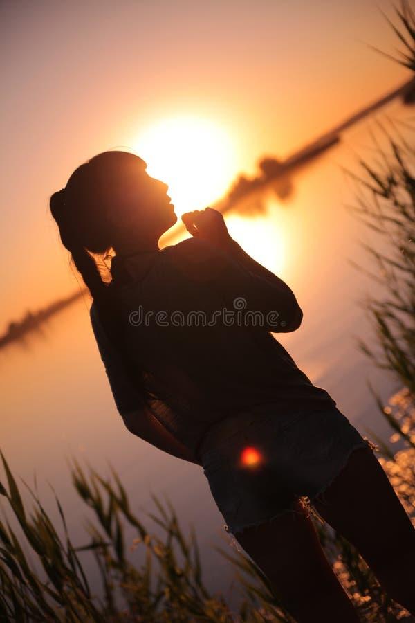 Ragazza nel lago al tramonto fotografia stock libera da diritti