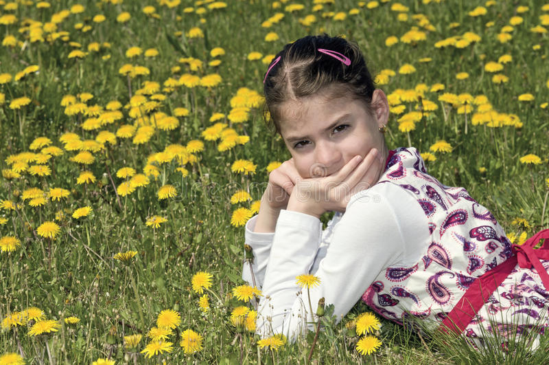 Ragazza nel prato di fioritura che esamina macchina fotografica immagini stock libere da diritti