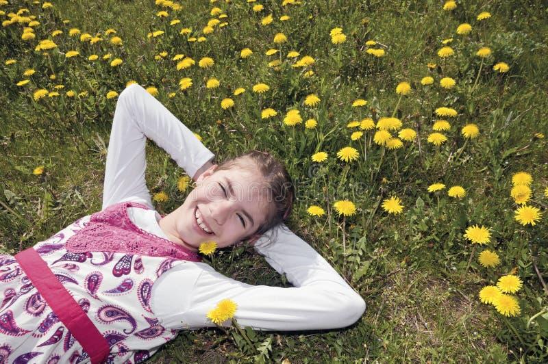 Ragazza nel prato di fioritura su lei indietro fotografie stock