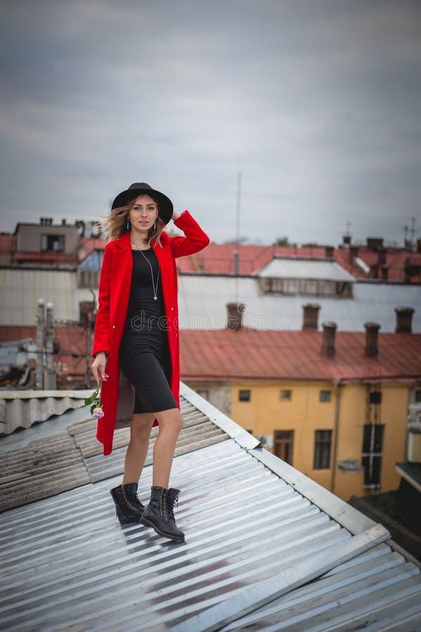 Ragazza nel rosso e con la posa black hat sul tetto di vecchia città immagini stock libere da diritti